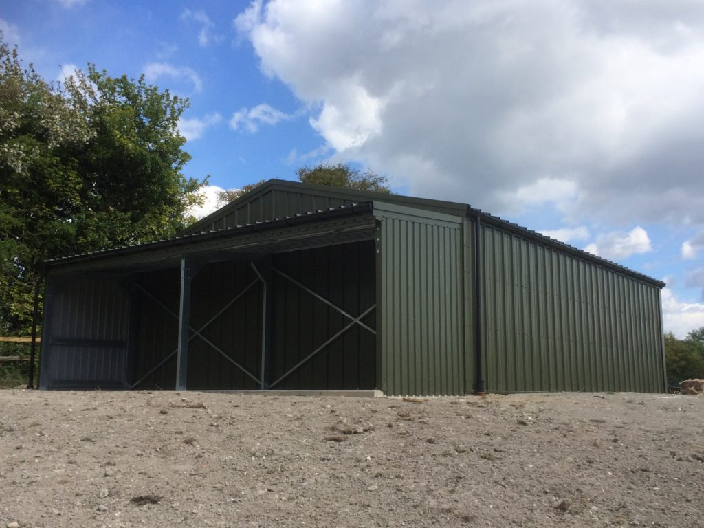 Olive green agricultural building with a rear gable end lean to extension
