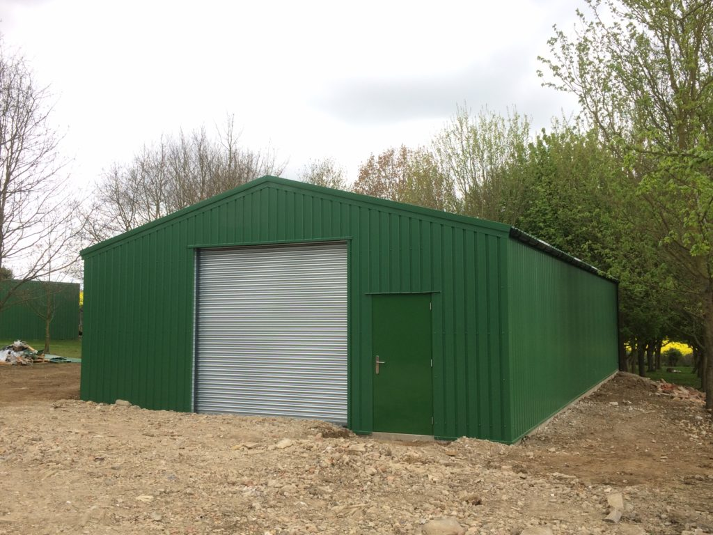 Forest Green coloured storage building set on a hardcore surround