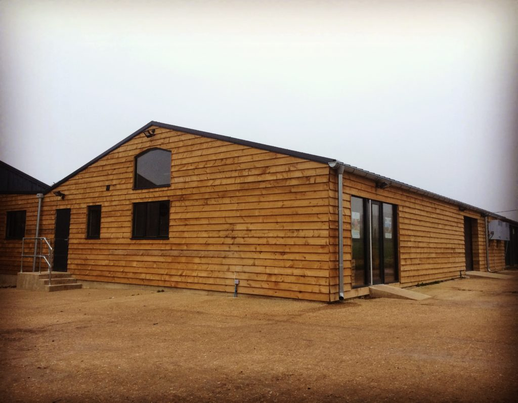Wood clad farm shop building with glass front doors
